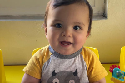 baby with yellow shirt smiling