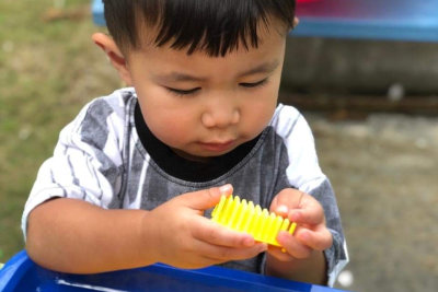 kid holding a yellow toy